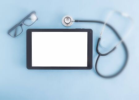 Computer tablet with a white screen on a blue background and glasses for vision, a stethoscope. The concept of selection of glasses in ophthalmology, eye diseases, place for text