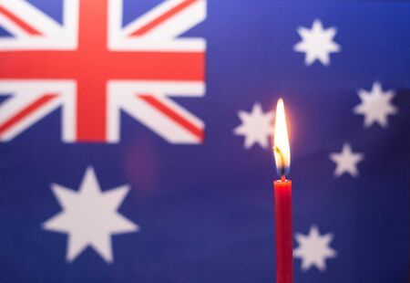 Burning candle on the background of the flag of Australia. The concept of mourning and sorrow in the country 스톡 콘텐츠