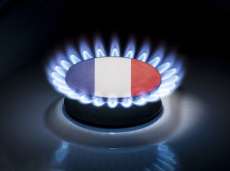 Burning gas burner of a home stove in the middle of which is the flag of the country of France. Gas import and export delivery concept, price per cubic meter, transit, background, gasoline