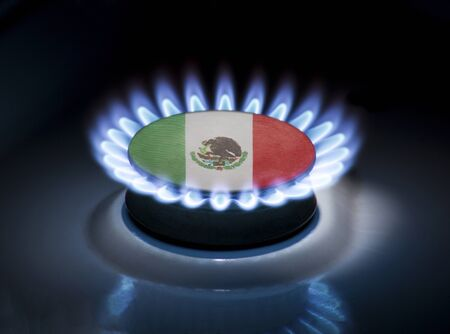 Burning gas burner of a home stove in the middle of which is the flag of the country of Mexico. Gas import and export delivery concept, price per cubic meter, transit, background, gasoline 스톡 콘텐츠