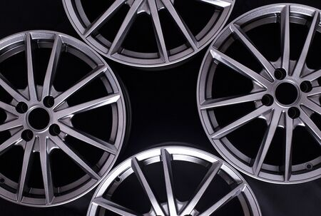Modern automotive alloy wheel made of aluminum on a black background, industry. Designer fashion wheels for car, mechanic