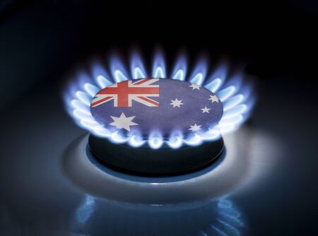 Burning gas burner of a home stove in the middle of which is the flag of the country of Australia. Gas import and export delivery concept, price per cubic meter, transit, background, gasoline 스톡 콘텐츠