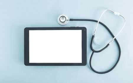 Computer tablet with a white screen on a blue background and a stethoscope. The concept of introducing electronic tablets and gadgets into medicine, a patient s electronic card, background
