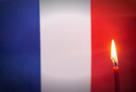 Burning candle on the background of the flag of France. The concept of mourning and sorrow in the country