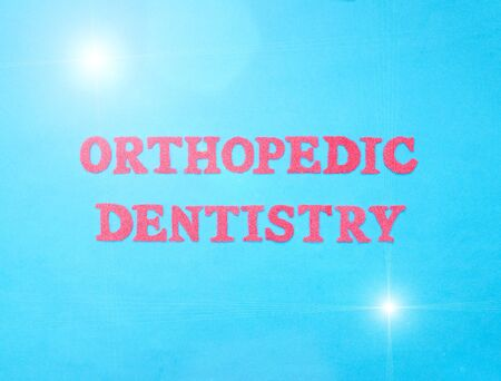 The word orthopedic dentistry in red letters on a blue background. The concept of the section of dentistry dealing with prosthetics in the oral cavity