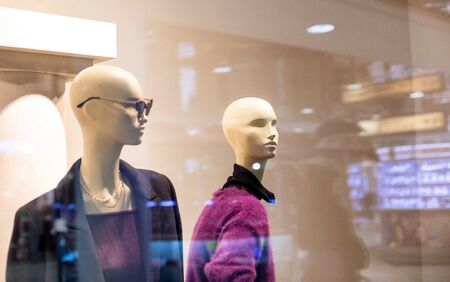 Two fashionable and stylish mannequins in modern glasses and warm business clothes. The concept of selling quality and stylish clothes