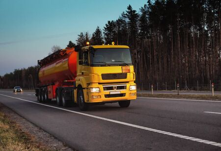 A truck carries a tank of combustible fuel on a highway against a forest and blue sky. The concept of transportation of dangerous goods on the road