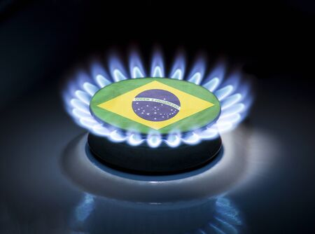 Burning gas burner of a home stove in the middle of which is the flag of the country of Brazil. Gas import and export delivery concept, price per cubic meter, transit, background, gasoline