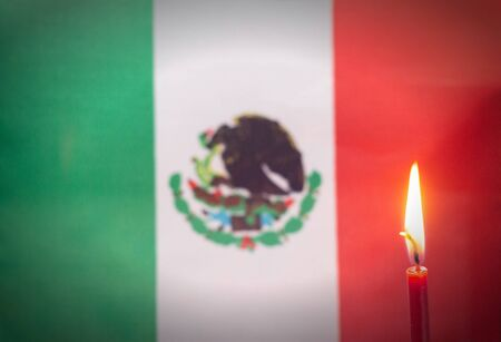 Burning candle on the background of the flag of Mexico. The concept of mourning and sorrow in the country