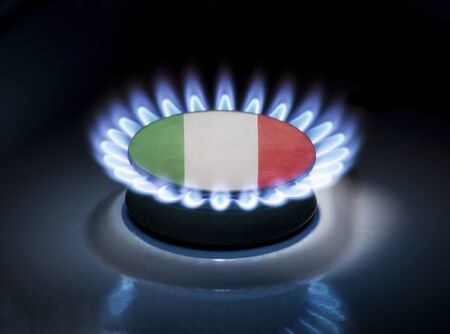 Burning gas burner of a home stove in the middle of which is the flag of the country of Italy. Gas import and export delivery concept, price per cubic meter, transit, background, gasoline
