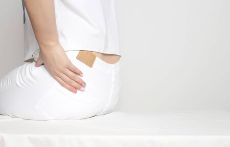 A girl in white clothes holds by the hip in which pain and inflammation. Femur Osteoarthritis Concept