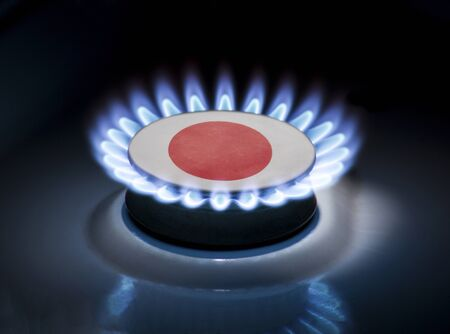 Burning gas burner of a home stove in the middle of which is the flag of the country of Japan. Gas import and export delivery concept, price per cubic meter, transit, background, gasoline Stock Photo