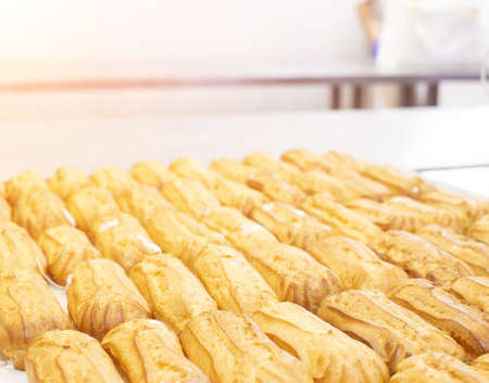 Confectionery for the production of desserts and sweets, making custard cake eclairs with cream and coconut