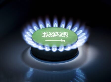 Burning gas burner of a home stove in the middle of which is the flag of the country of Saudi Arabia. Gas import and export delivery concept, price per cubic meter, transit, background, gasoline
