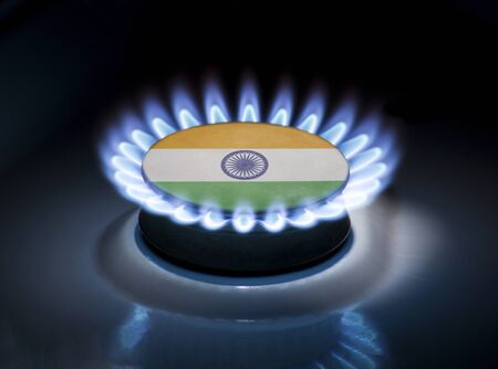 Burning gas burner of a home stove in the middle of which is the flag of the country of India. Gas import and export delivery concept, price per cubic meter, transit, background, gasoline Stock Photo