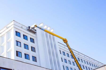 Repair and reconstruction of the facade of the building with the help of a worker and a car tower. Blue sky industry, copy space, engineering