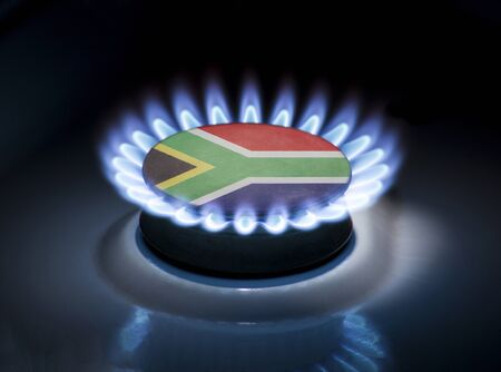 Burning gas burner of a home stove in the middle of which is the flag of the country of South Africa. Gas import and export delivery concept, price per cubic meter, transit, background, gasoline Stock Photo