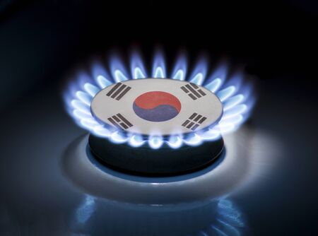 Burning gas burner of a home stove in the middle of which is the flag of the country of South Korea. Gas import and export delivery concept, price per cubic meter, transit, background, gasoline Stock Photo