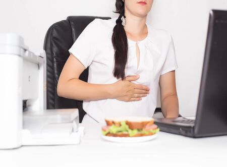Girl office worker near which lies a sandwich holding on to a stomach in which there is pain and inflammation in the stomach. Concept of indigestion and malnutrition in office workers, gastritis and duodenal ulcer, problem
