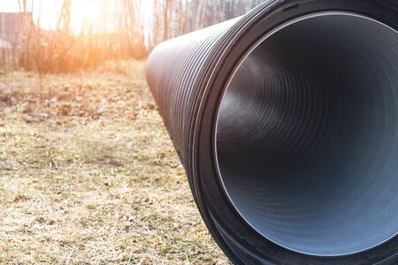 Large diameter black polypropylene pipes for laying communications, drainage systems and heating mains under the road. Modern method and technology for supplying water and sewage, copy space Banque d'images