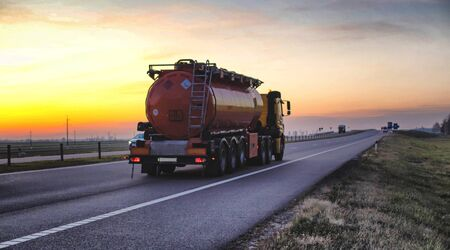 A truck carries a tank of combustible fuel on a highway against a forest and blue sky. The concept of transportation of dangerous goods on the road, license