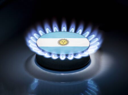 Burning gas burner of a home stove in the middle of which is the flag of the country of Argentina. Gas import and export delivery concept, price per cubic meter, transit, background, gasoline