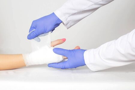 An orthopedic doctor wraps a bandage around a tight bandage on a broken palm and phalanx of the patient s fingers. Concept of fractures of the fingers on the hand