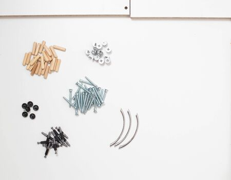 furniture assembly parts tie screws and wooden dowels, copy space, background
