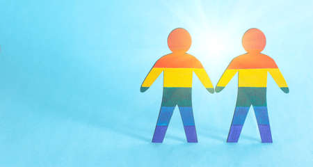Two wooden male figures painted in multi-colored LGBT symbols. The concept of homosexuality and gay men, gay marriage Standard-Bild