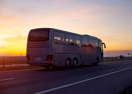 A large comfortable passenger bus against the orange sky with sunset rides on the highway. The concept of European passenger transportation in companies