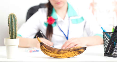 Black banana in the foreground in the office of a doctor of a sex therapist. The concept of the problem in men is a weakening of erectile dysfunction, a weak erection, a problem with potency and libido, disease