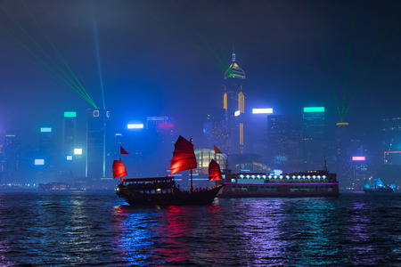 sha: Hong Kong Victoria harbour at night with traditional Chinese style boat