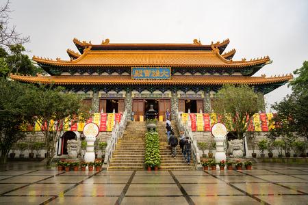 Ngong Ping village, Lantau island - Hong Kong. April 25 - 2017: Some tourists are visiting Po Lin monastary main hall during rain shower and cloudy morning