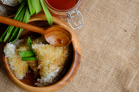 Kue lupis as traditional Indonesian sweet sticky rice dumplings of glutinous rice with grated or shredded coconut and palm sugar syrup Stock Photo