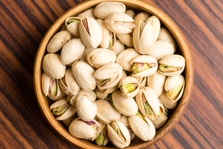 Salted Pistachio nuts in wooden bowl