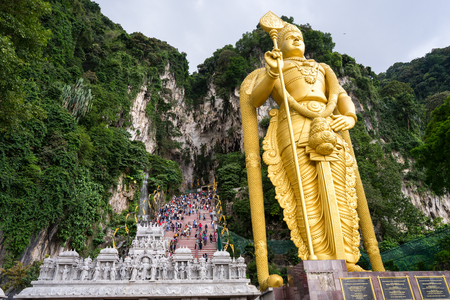 Gombak, Selangor - Malaysia. 2017 Sept 01: Entrance to Batu Caves with the worlds tallest Murugan deity statue stand tall in front of it. Редакционное