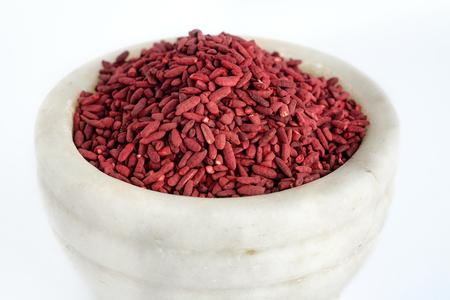 Riz fermenté à la levure rouge sur bol de broyage de mortier