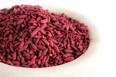 Red yeast fermented rice on mortar grinding bowl Banque d'images