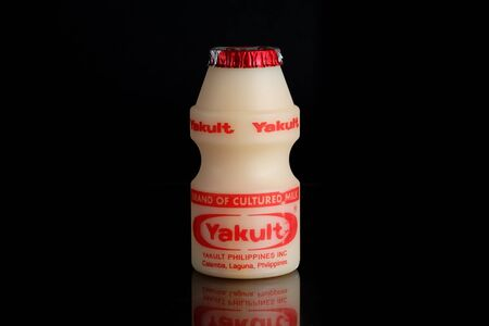 Makati city of Manila, Philippines. May 29 2019: Yakult fermented milk drink on black isolated background. Healthy probiotic drink with the bacteria strain Lactobacillus paracasei Shirota.