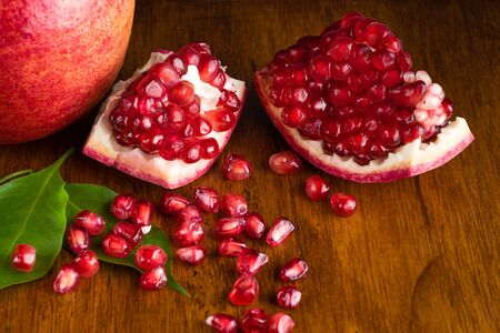Split open Pomegranate fruit or Punica granatum on wooden table Stock fotó