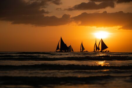 Silhouette Paraw sailing boats under orange sunset at Boracay Island of Philippines