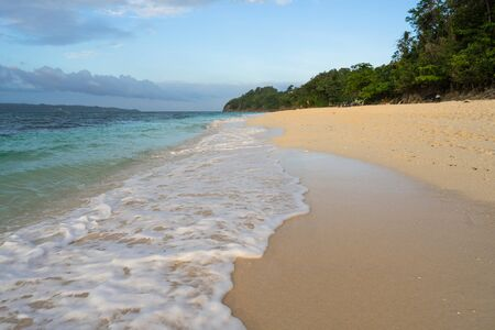 Beautiful Boracay Puka beach with sea foam from water waves and blue water during sunset