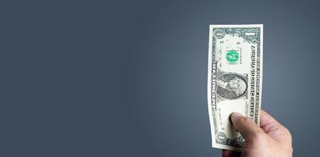 Young man holding small dollar bill Standard-Bild