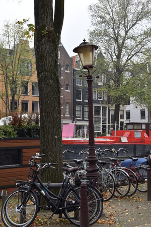 Lamppost with bicycles along the canal in Amsterdam Netherlands Stock Photo
