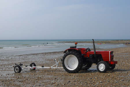 a red tractor with boatscart on a sandstrand in North France