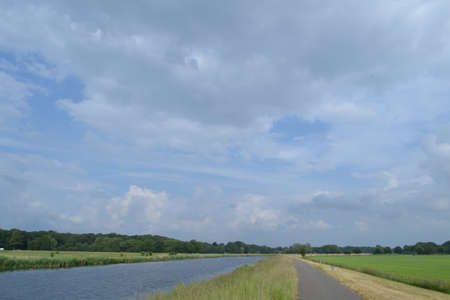 ijssel: Old river IJssel under clouded sky with road biking