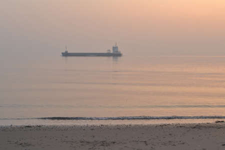 sunset with ship westerschelde beach near Zoutelande. Stock Photo