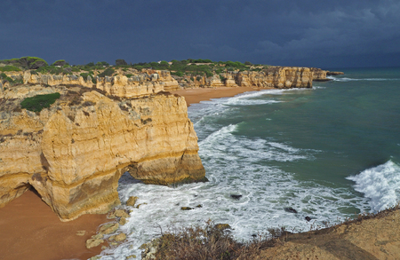 Blue sea shore with sandstone cliffs and dark blue sky