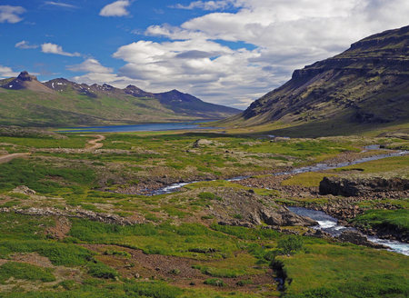 wonderful river valley with eroded snow spotted mountains and lake in west Iceland with blue sky and white puffy clouds
