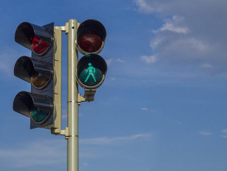 traffic light - semaphore - green walking figure puppet on blue sky background